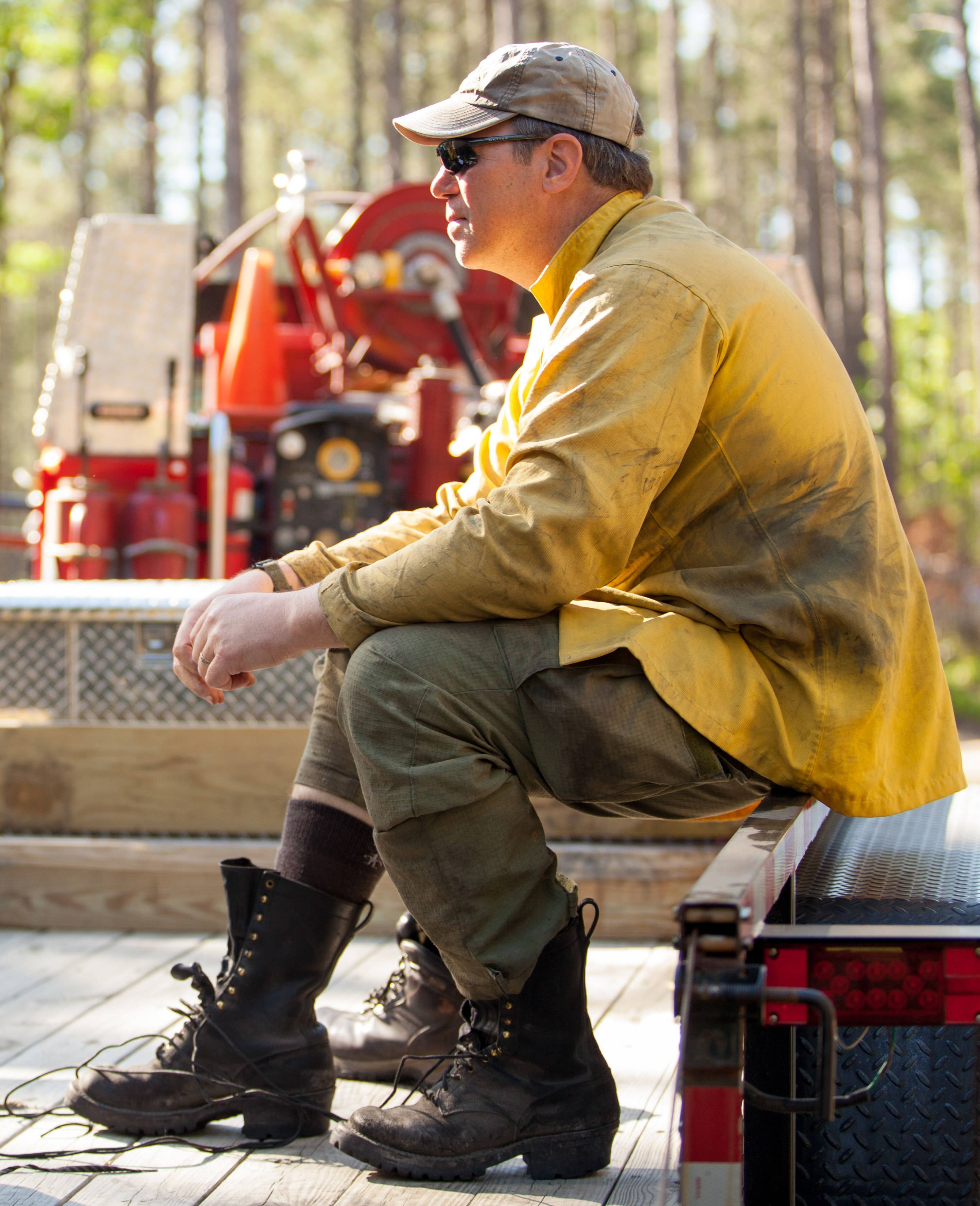 A man wearing sunglasses and a soot streaked yellow shirt sits and rests at the end of a controlled burn.