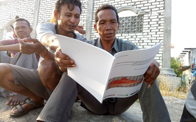 Three men sit on the ground and look at a book about fish.
