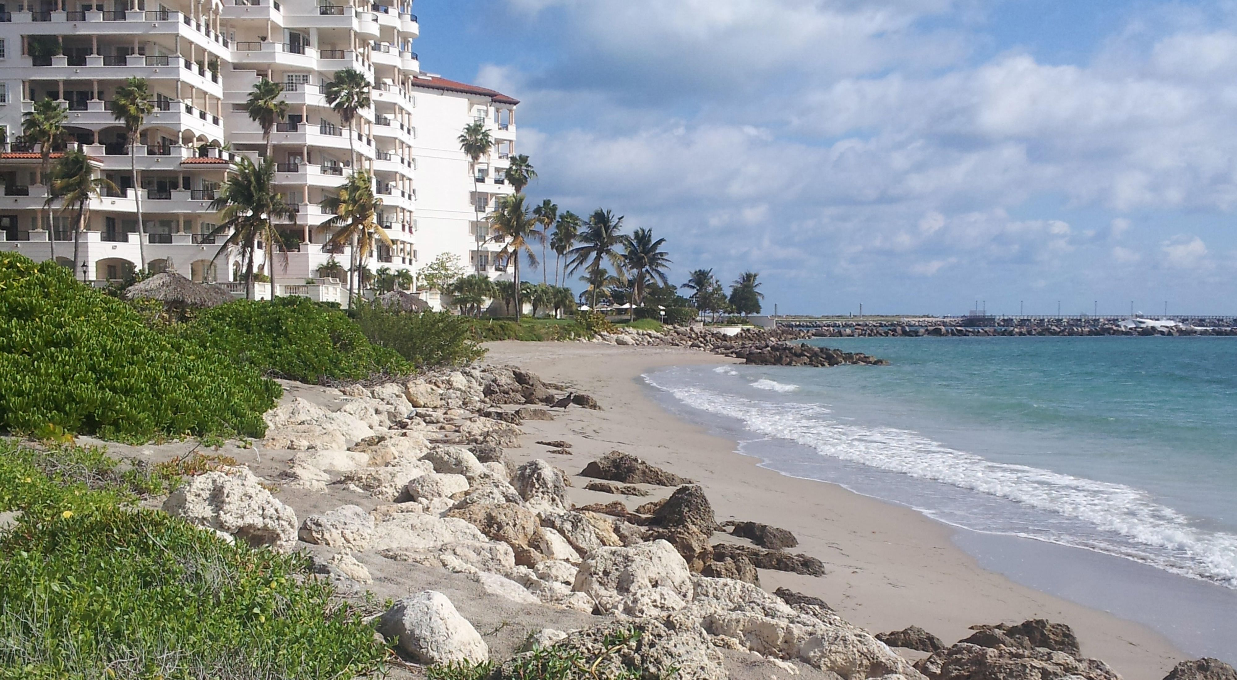 A highrise condominium building sits very near to the ocean shoreline with blue water, rocks and a sandy beach in Fisher Island, located in the Miami, Florida metropolitan are