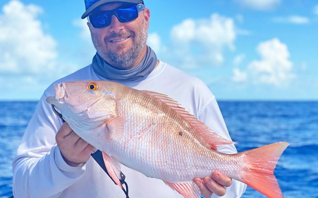Fisherman holds a freshly caught mutton snapper in the Florida Keys.