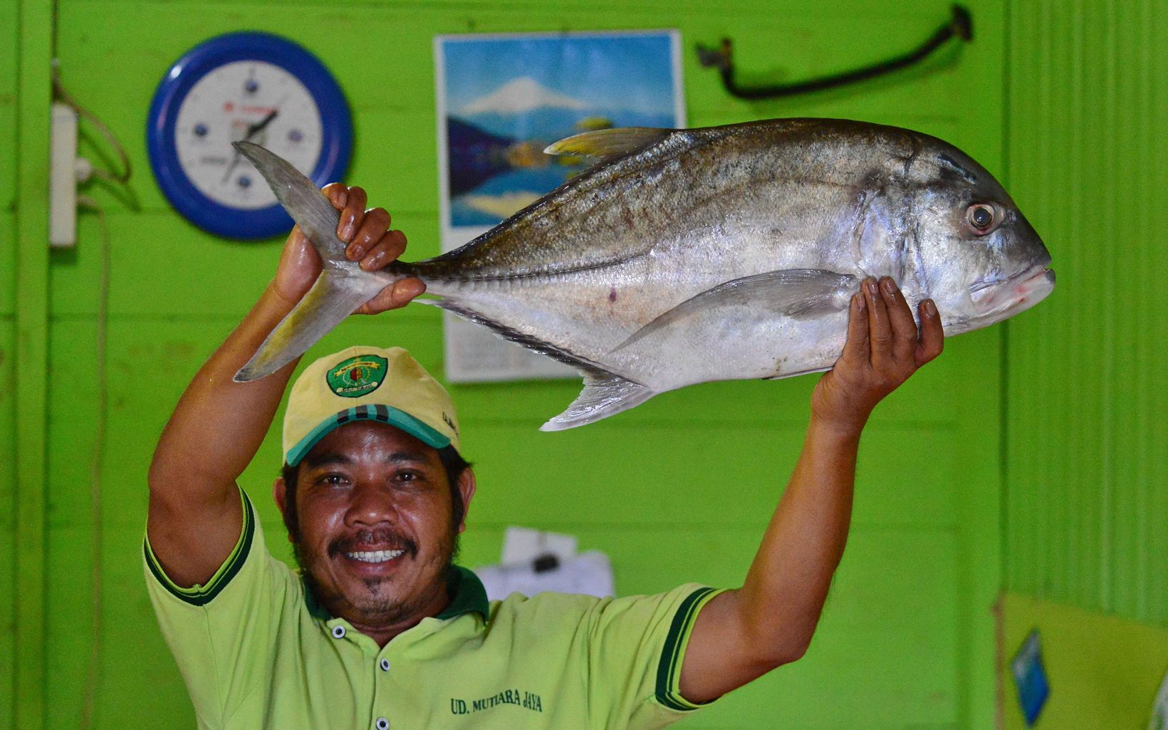 Fisherman from the coastal village of Semanting proudly displays his prize catch. Semanting is a SIGAP partner village in Borneo.