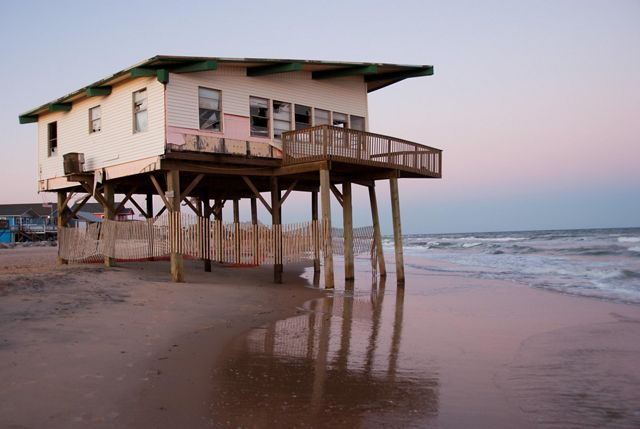 An endangered house in wait of advancing sea level and coastal storms along the Gulf Coast near Freeport, Texas.