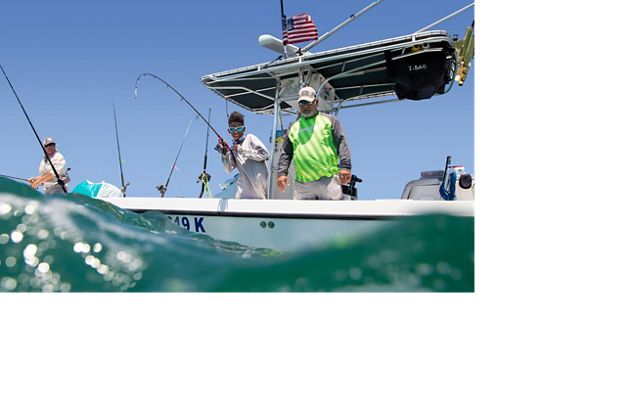 View from just above the waves of three people fishing from the side of a boat in the Florida Keys.