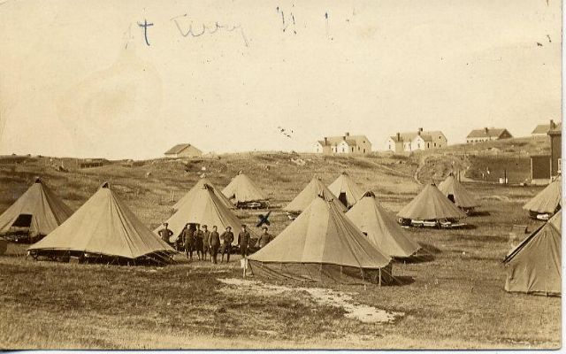 Historical photo of Army base Fort Terry showing 12 tents in foreground and buildings in the background.