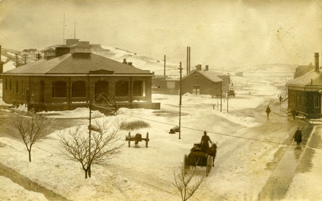 Historical photo of a town square like setting at Army base Fort Terry, with snow on the ground and a horse drawn carriage in foreground.