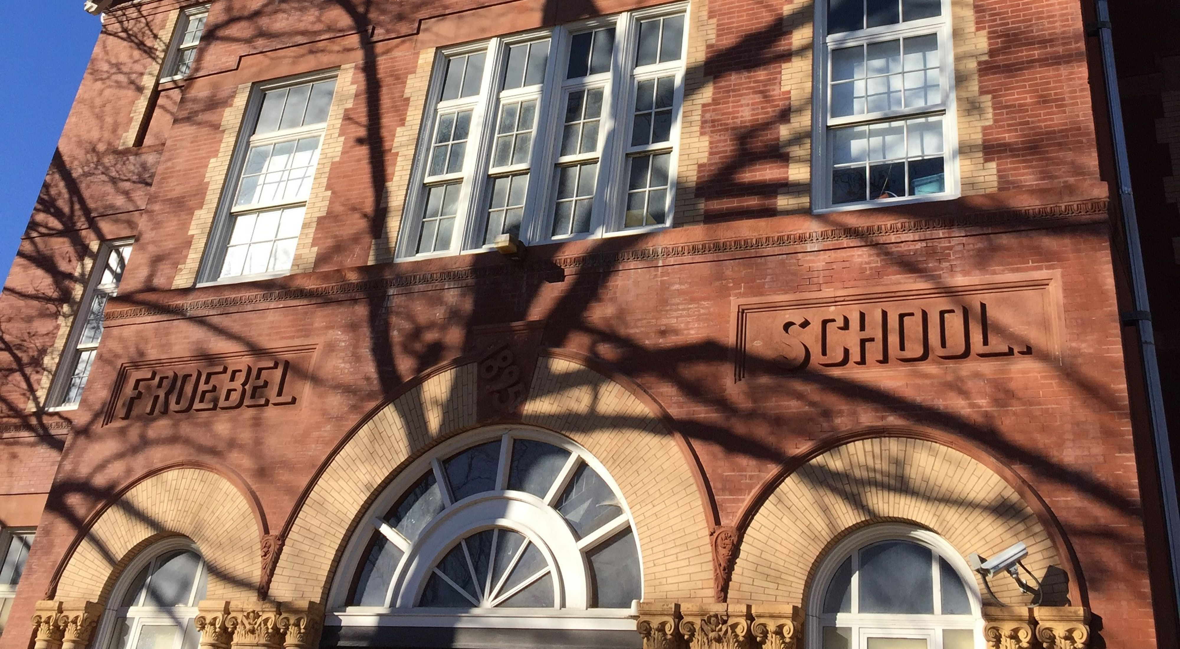 The brick facade of Froebel Literacy Academy in St. Louis, with the words Froebel School in raised lettering.
