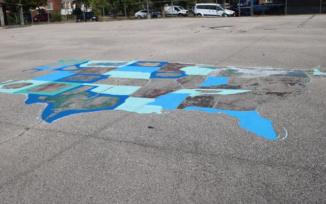 An outline of the United States map is painted on a paved schoolyard.