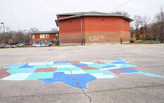 A large paved schoolyard with a map of the U.S. painted on it in front of a red-brick building.