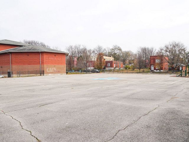 A large paved schoolyard in front of a red-brick building in an city setting.