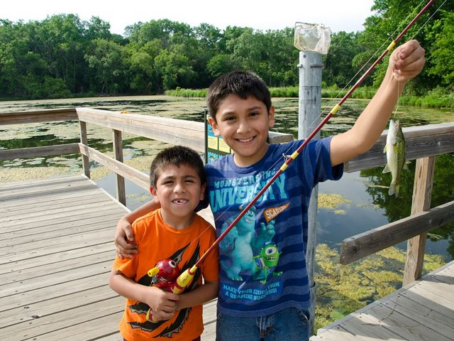Two young boys hold up their catch from a fishing pier