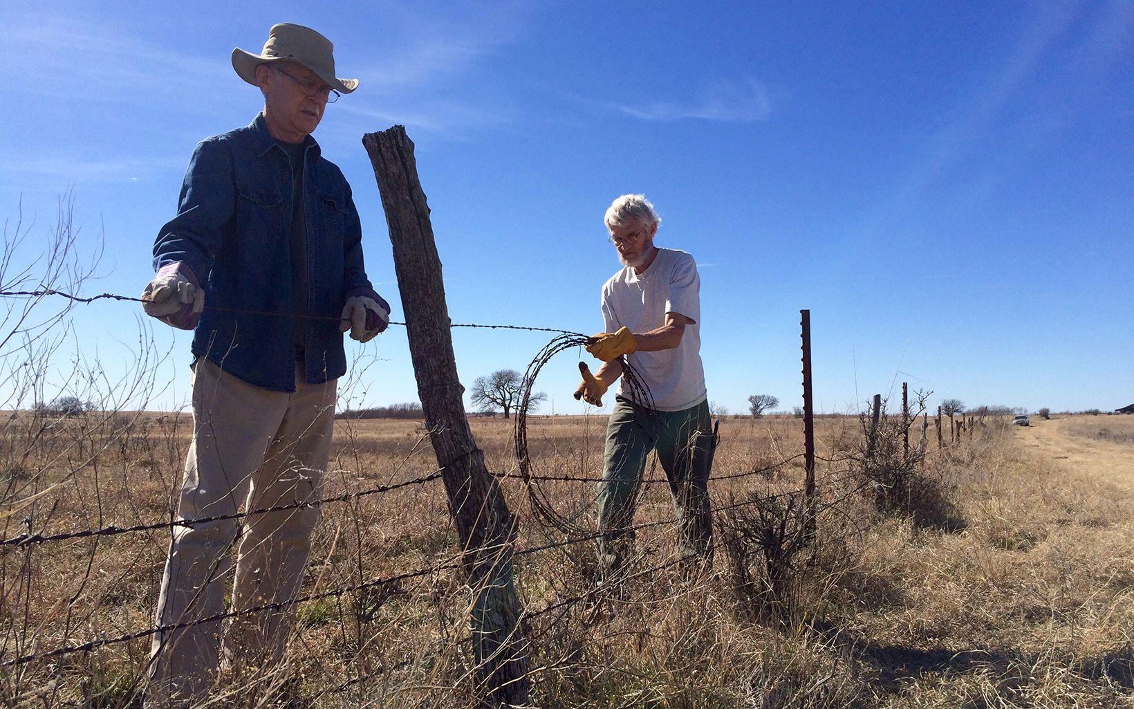 Volunteer removing fencing along Blue River