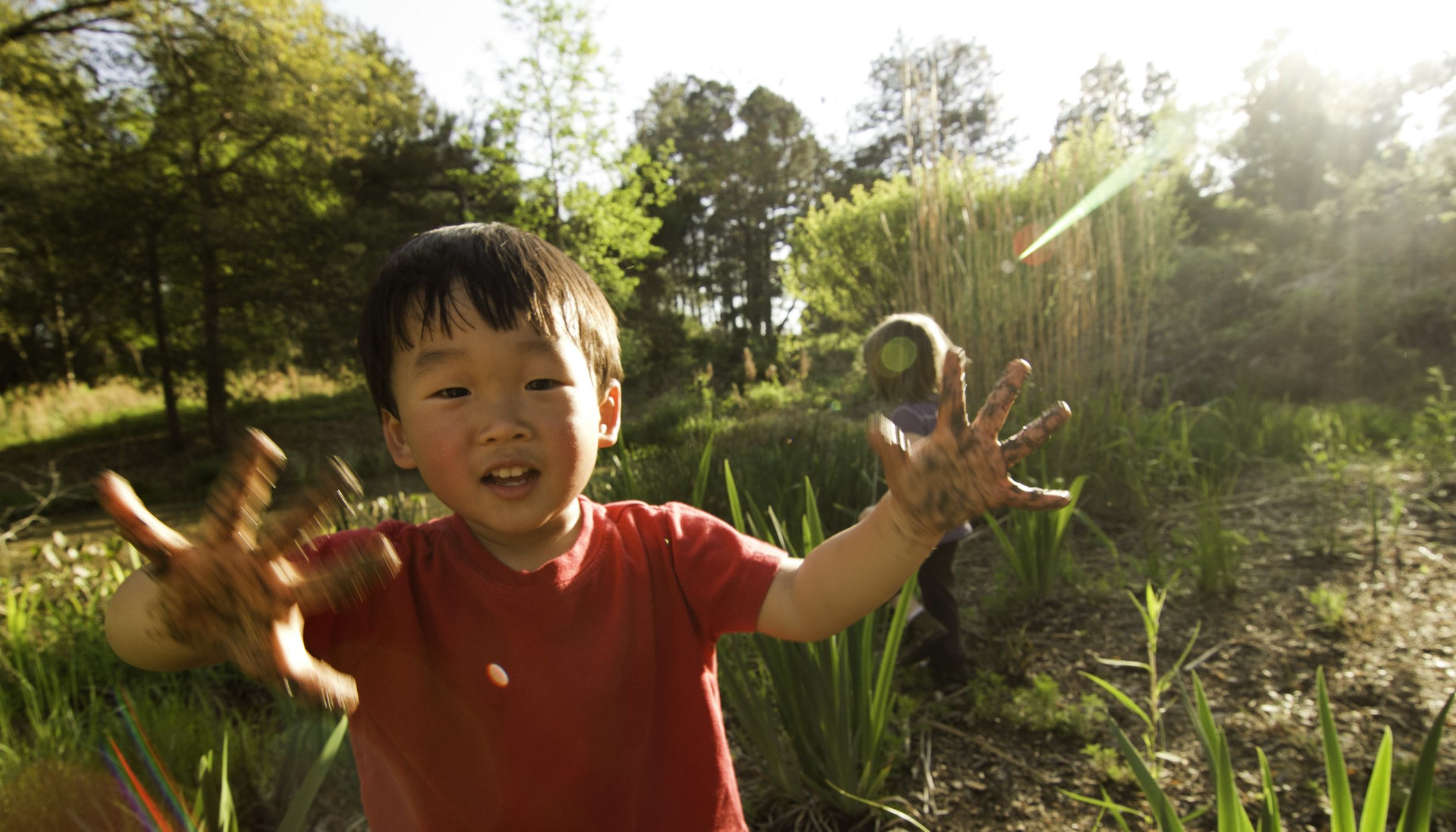 smiling toddler stands in a green space with mud on his hands.