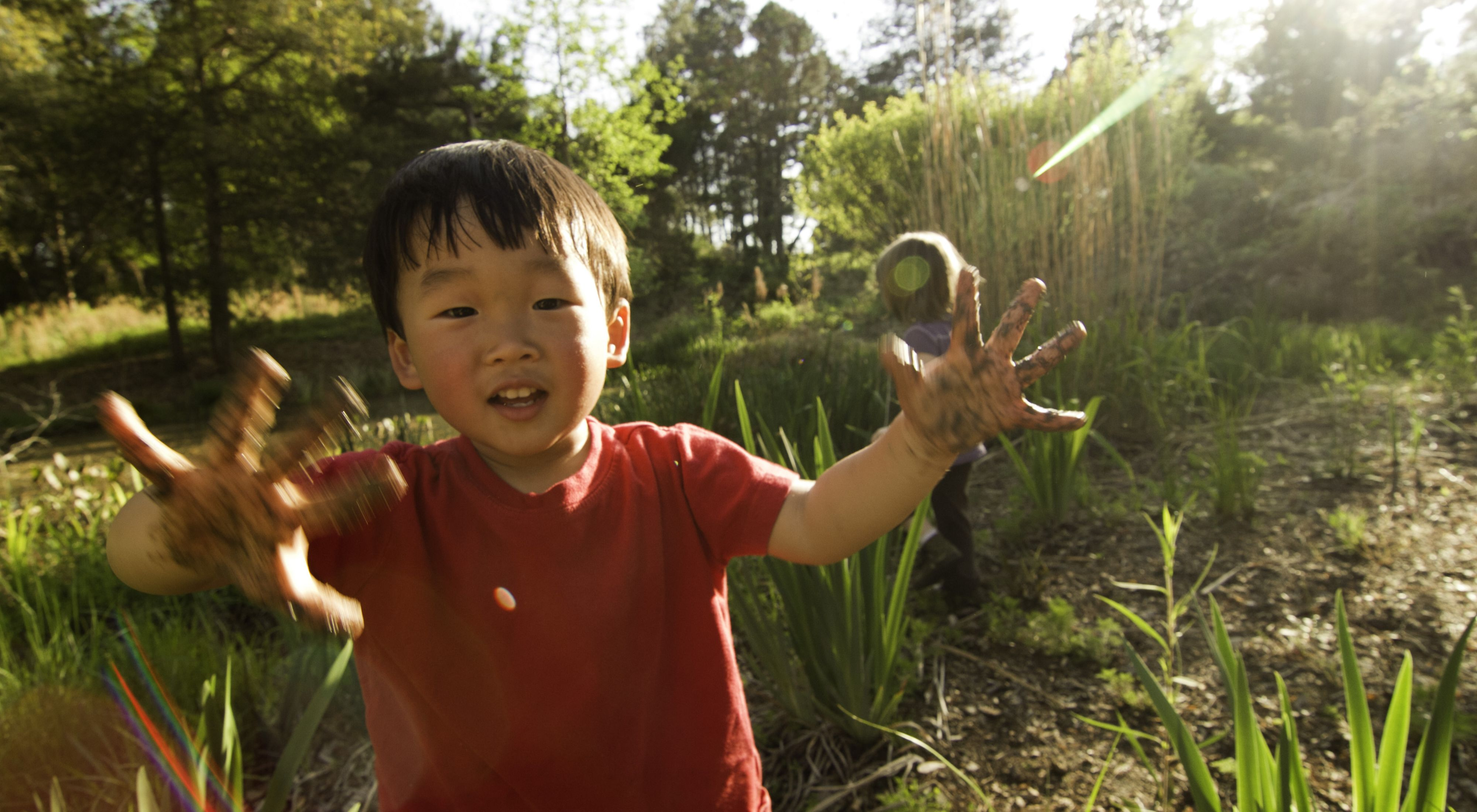 Toddler walks in forested area with mud on his hands.