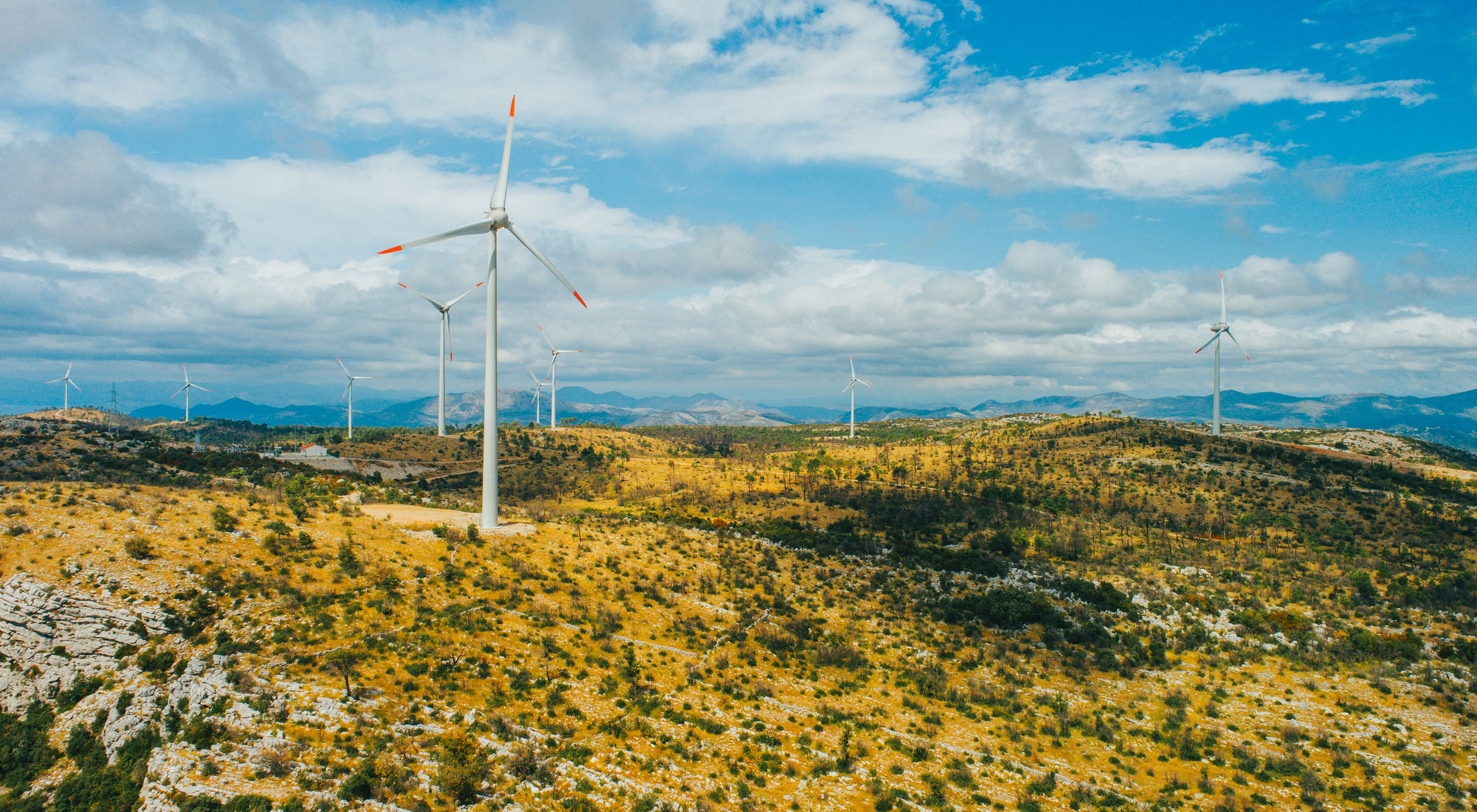 Scenic mountainous landscape with wind turbines against cloudy sky.