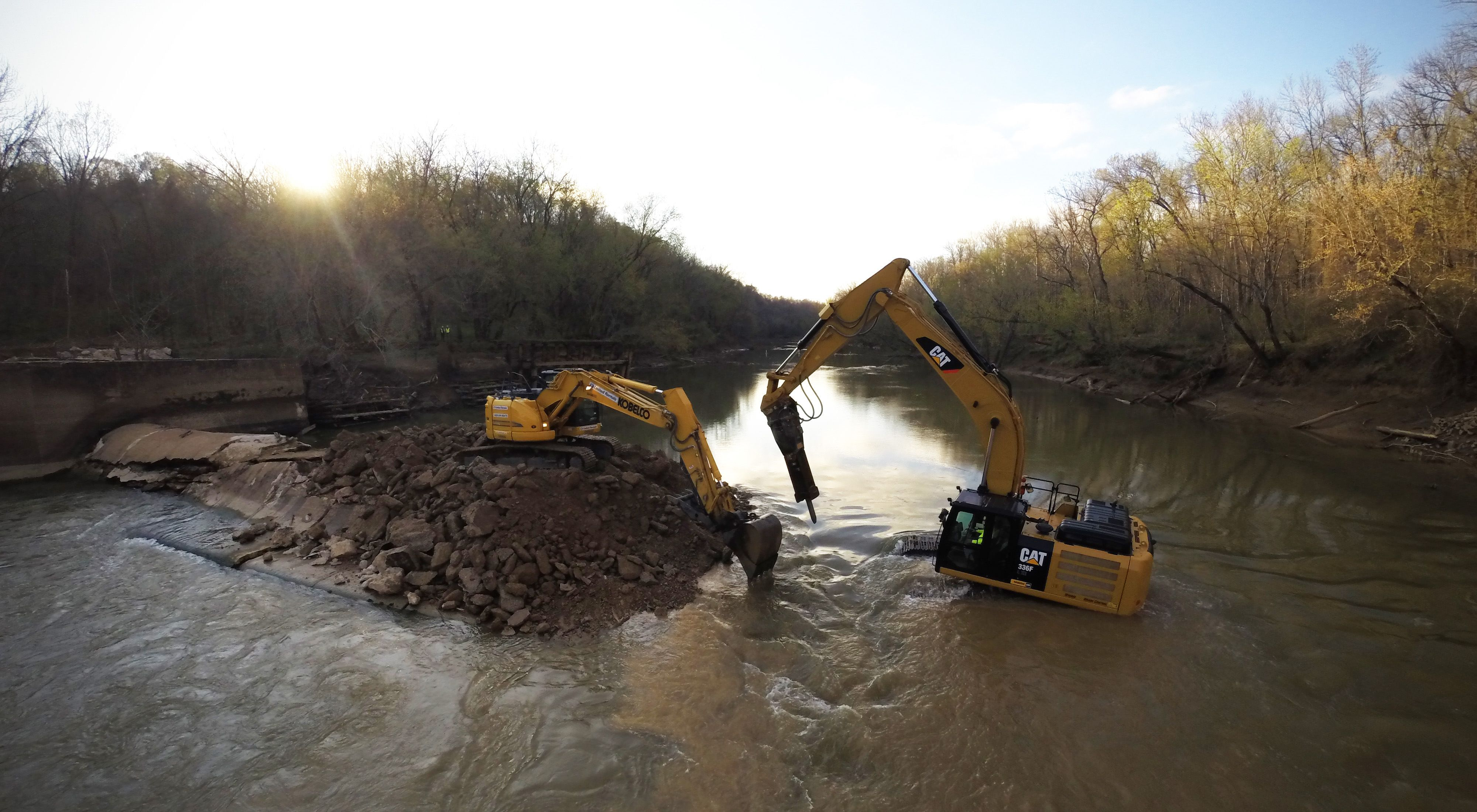 A dam is removed by heavy equipment.