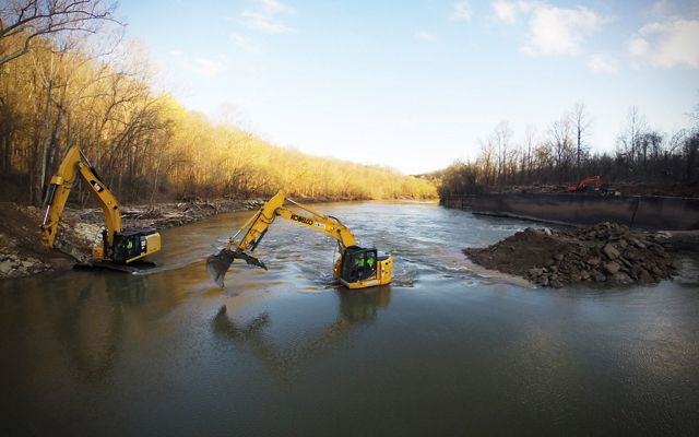 Yellow diggers sit mid-stream and remove debris from the river.