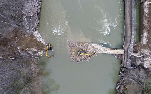 Aerial image of dam removal, looking down on diggers that have partially removed a concrete dam from the river.