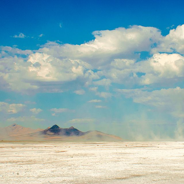 White dust blows on a dry lakebed under a blue sky with white clouds.