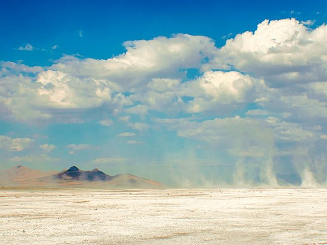 White dust blows across a sandy lakebed under a blue sky peppered with fluffy white clouds.