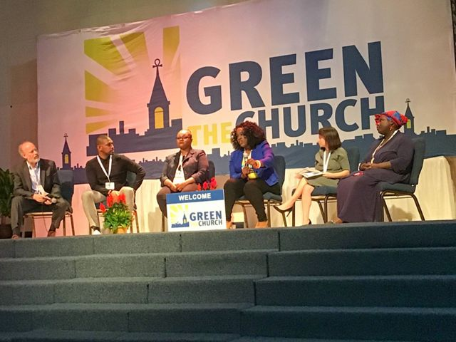 A panel of six people sitting in chairs on a stage in front of a banner reading 'Green The Church.'