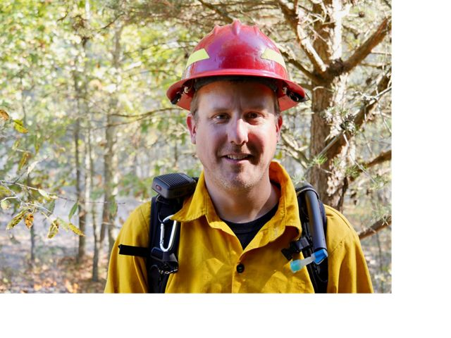 A smiling man wearing yellow protective fire gear and a red hardhat stands in a forest during a controlled burn.