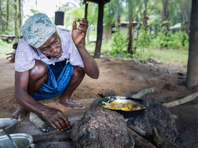 Woman crouches next to cooking fish