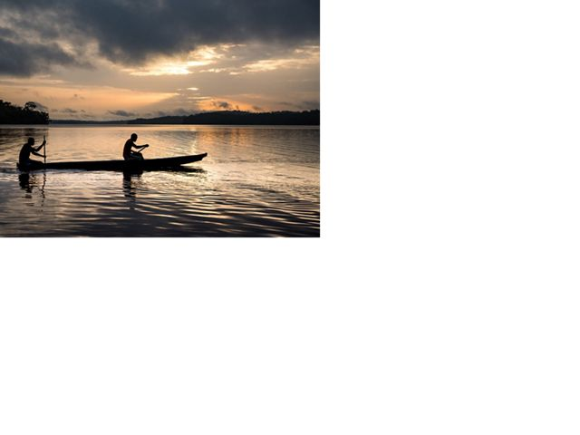 Two fishermen in a canoe at sunrise