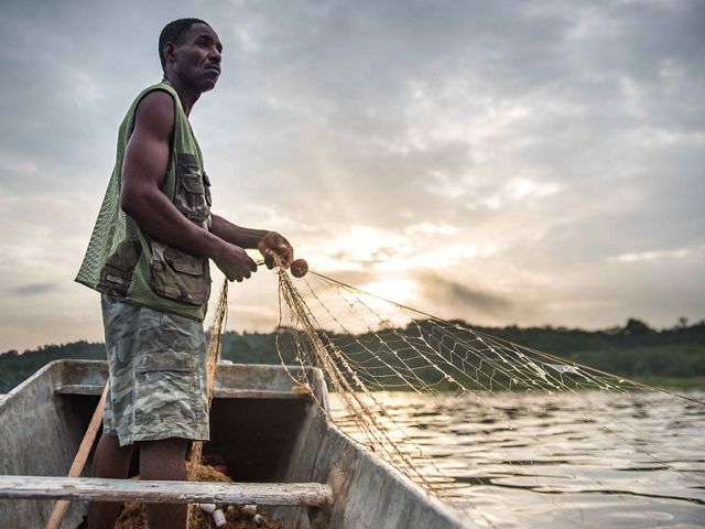 Man pulls a fishing net from a small boat