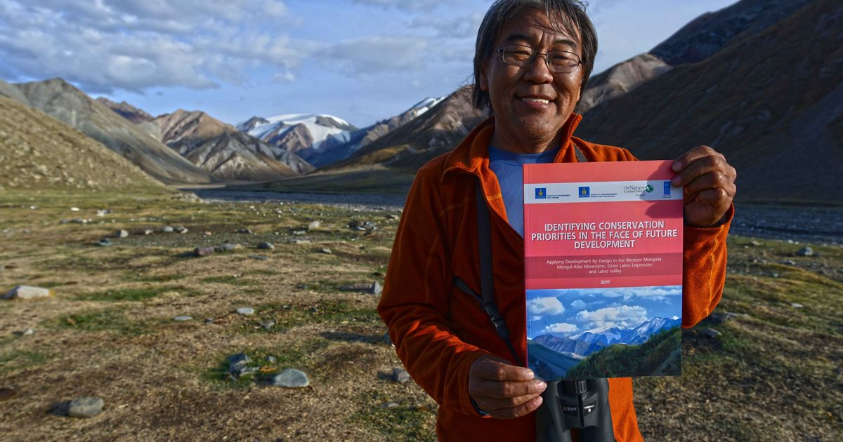 Portrait of Gala Davaa holding up a report about Western Mongolia.