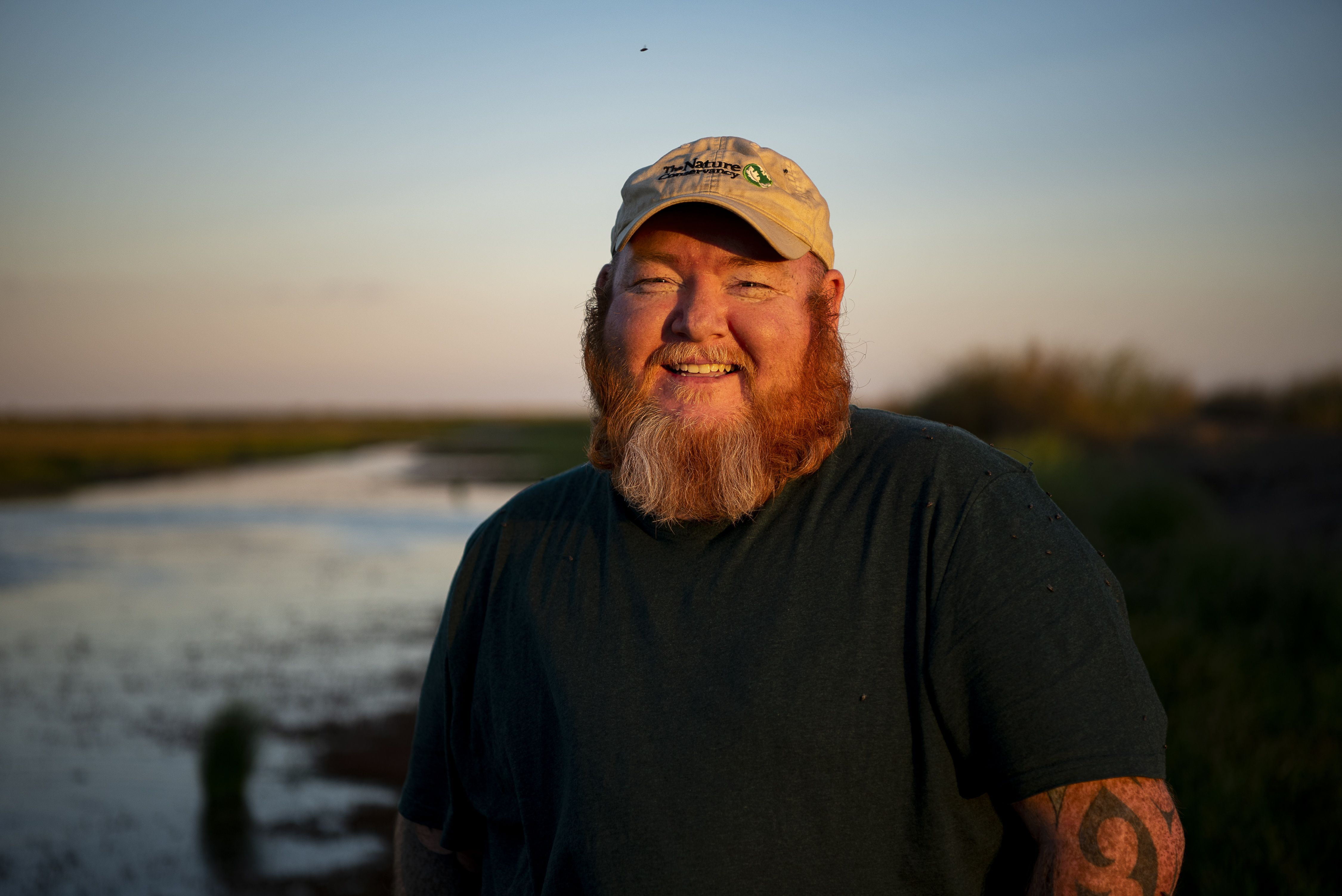 portrait of a bearded man at dusk, with a body of water behind him