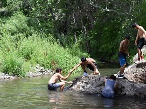 Four shirtless men play and work together on a river.