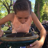 girl drinks water from a fountain