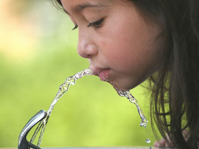 Girl drinking water from a water fountain.