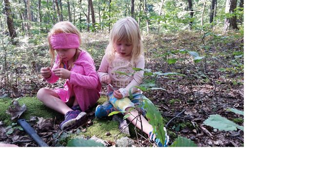 Two girls sit on the floor of a forest.