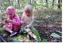 Two girls sit on a forest floor.