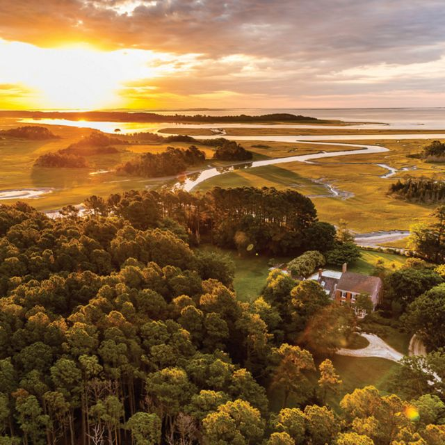 Aerial view of Brownsville Preserve. An historic brick home with a circular oyster shell driveway stands in a clearing between thick stands of trees. In the background the sun rises over the Atlantic.