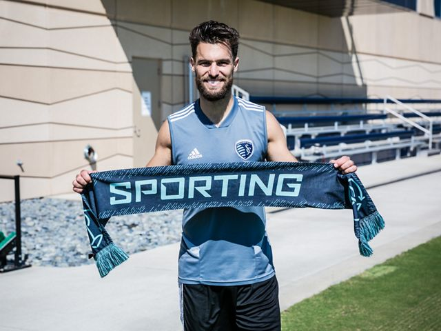 Sporting Kansas City's Graham Zusi holds a Sporting Sustainability match scarf.