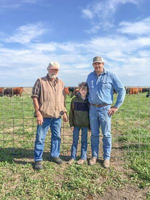 Two men and a boy standing in front of a fence with cattle in the background.