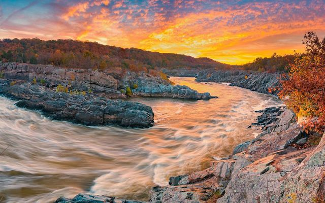 White rapids swirl and eddy as the Potomac River rushes through rocky formations at Great Falls as the sun rises.