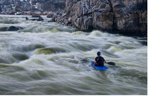 Swirling white water is a blur as it rushes past a man in a blue kayak, racing between the steep rocky sides of the channel.