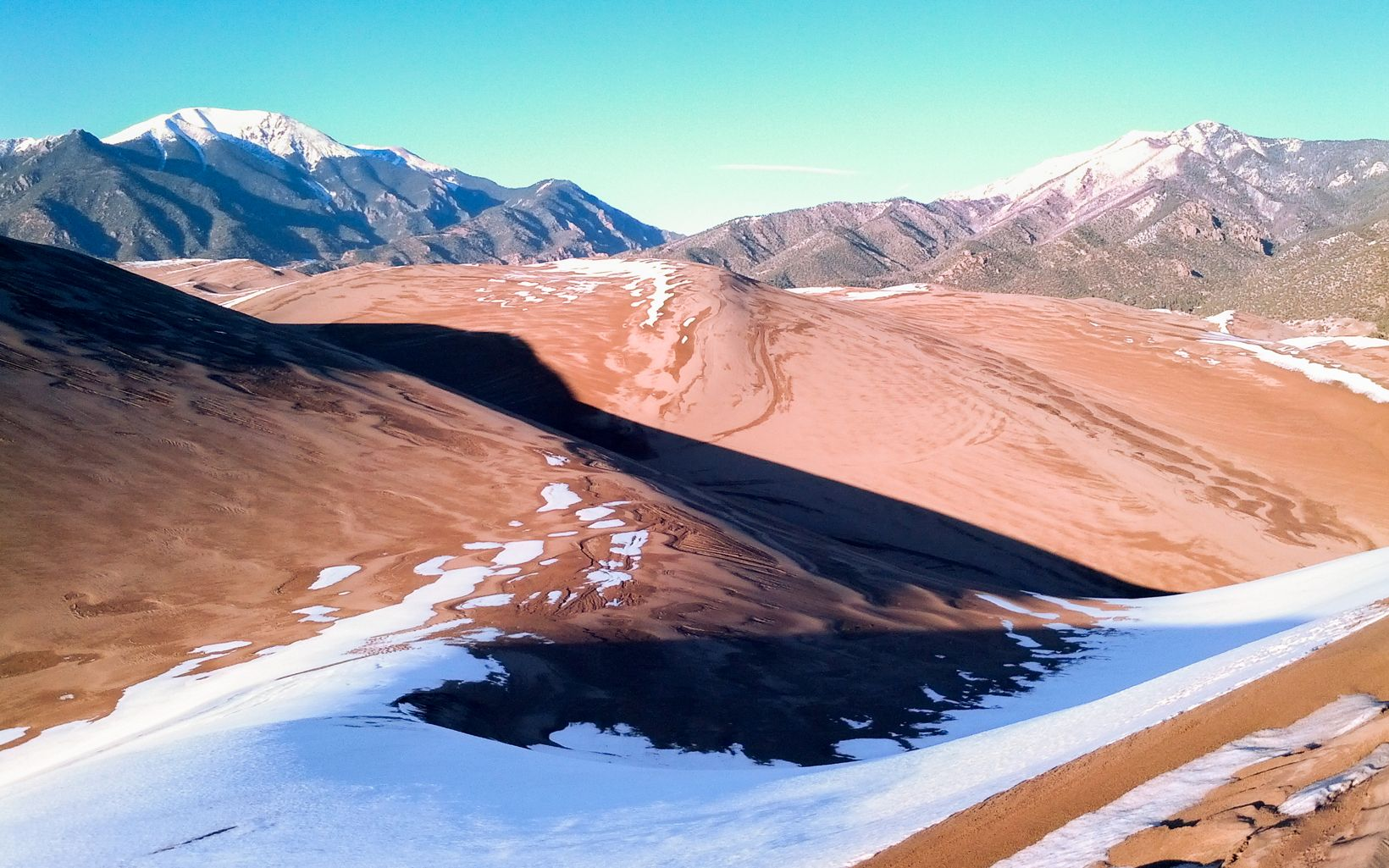Shadows fall across the snowy landscape at the Great Sand Dunes National Park in San Luis Valley, CO.