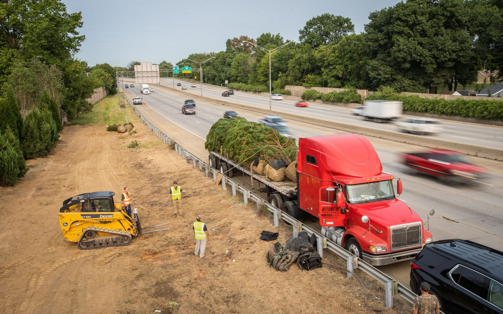 Trees being offloaded from a semi truck next to a highway.