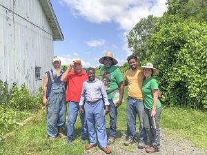 A group of individuals standing together outside on an urban farm.