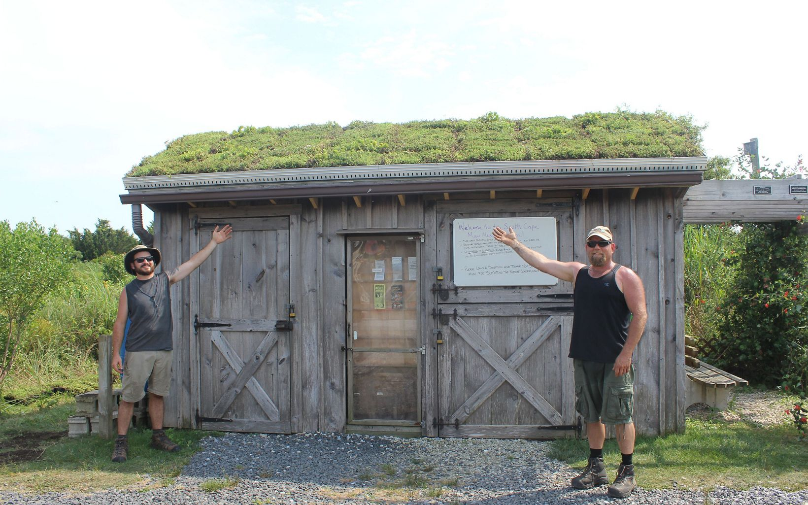 Two TNC employees are standing in front of a greeting center with a green roof.