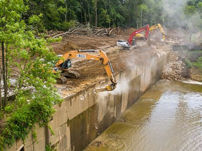 Large equipment hammers away at a large concrete structure on a river.