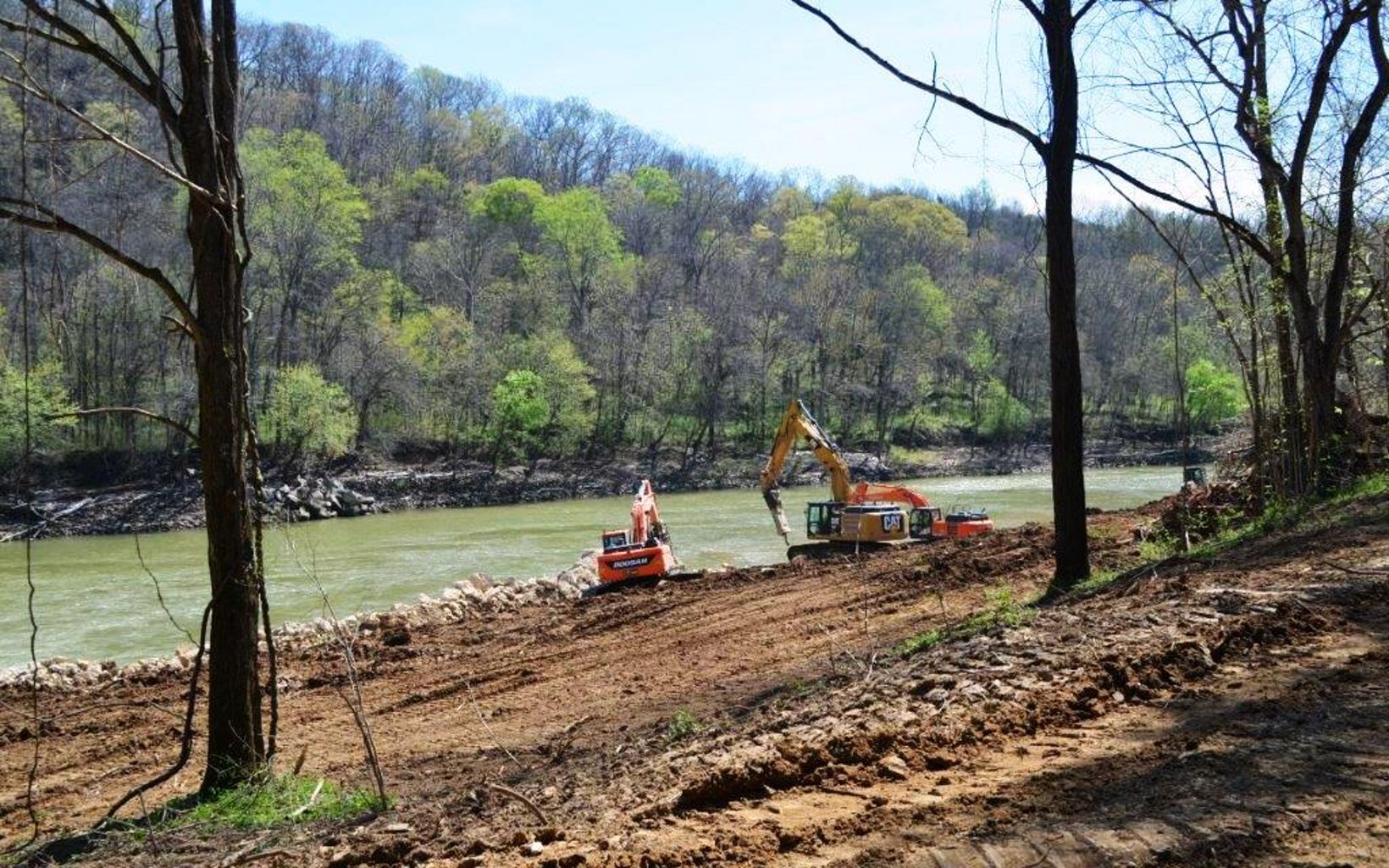 Heavy equipment sits along the side of a river.