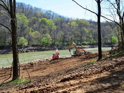 Construction equipment sits on a river bank.