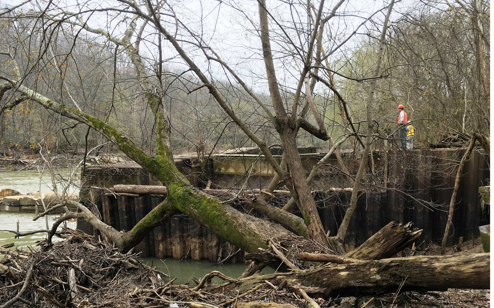 A man in orange examines a large steel structure near a river.