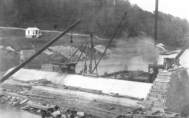 Historical black-and-white photo of cranes constructing the dam.