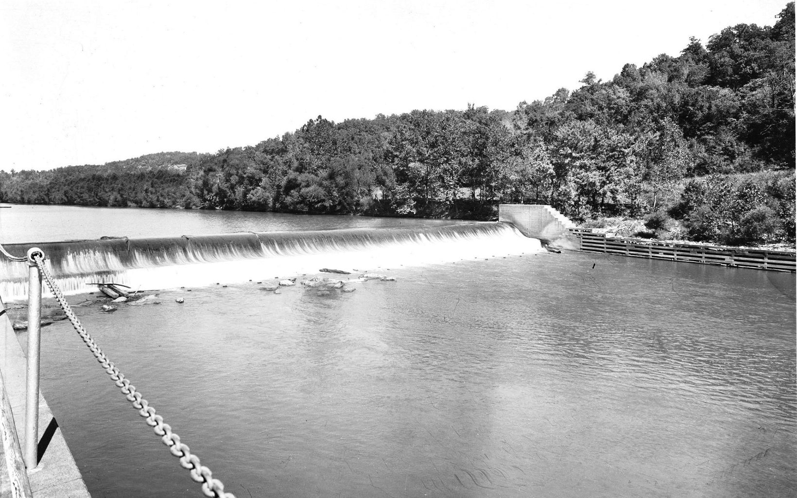 An historic image depicts a barge operating near a dam.